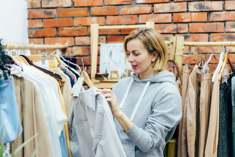 Candid woman shopaholic chooses fashionable clothes in the showroom.