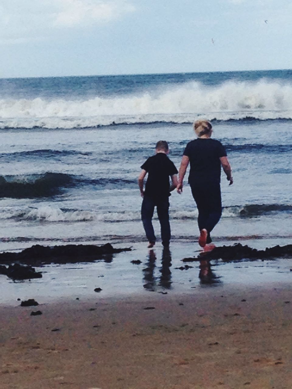 Rear View Of Mother And Son Walking Towards Sea At Beach