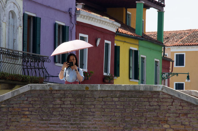 Adult Architecture Building Exterior Built Structure Burano Camera City Day Europe Italy Lifestyles One Person Outdoors Painted Houses Parasol People Real People Travel Venice Venice, Italy Women Young Adult Young Women