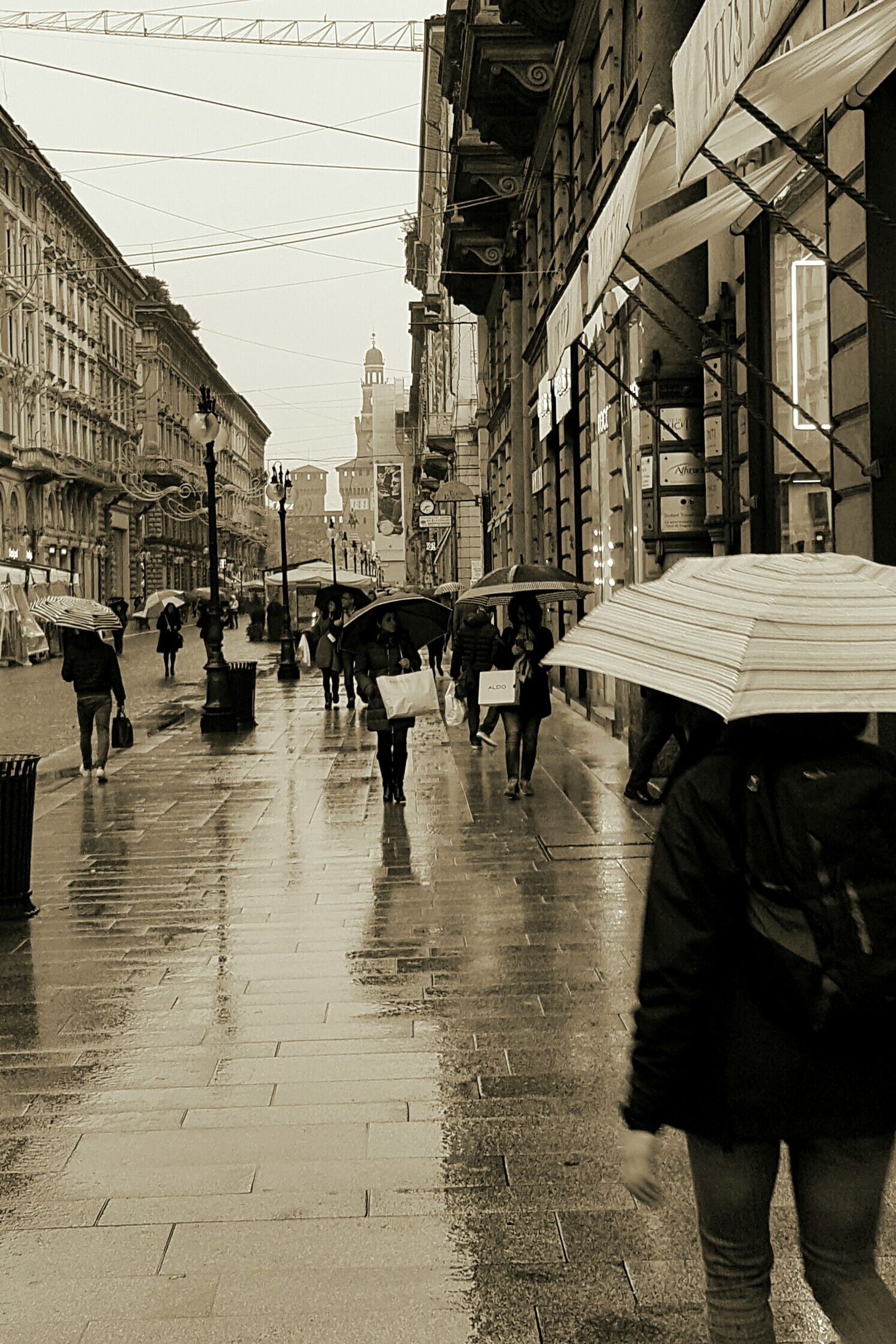 street, city, wet, building exterior, men, people, large group of people, adult, outdoors, water, adults only, extreme weather, day, architecture, only men