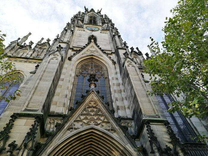 Low Angle View Architecture Religion Church Built Structure Building Exterior Place Of Worship Sky Arch Spirituality Façade Outdoors History Cloud - Sky Day Architectural Feature City Life Spire  Gothic Style