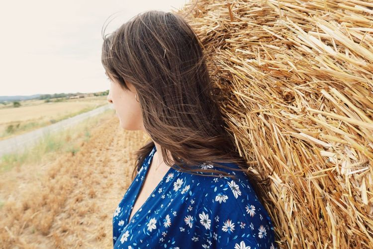 Side view of young woman leaning on hay bale