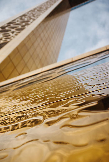 Close-up of metallic structure in sea against sky