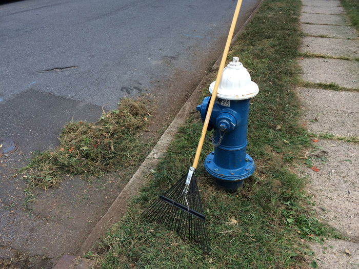 High Angle View Of Broom On Blue Fire Hydrant By Road