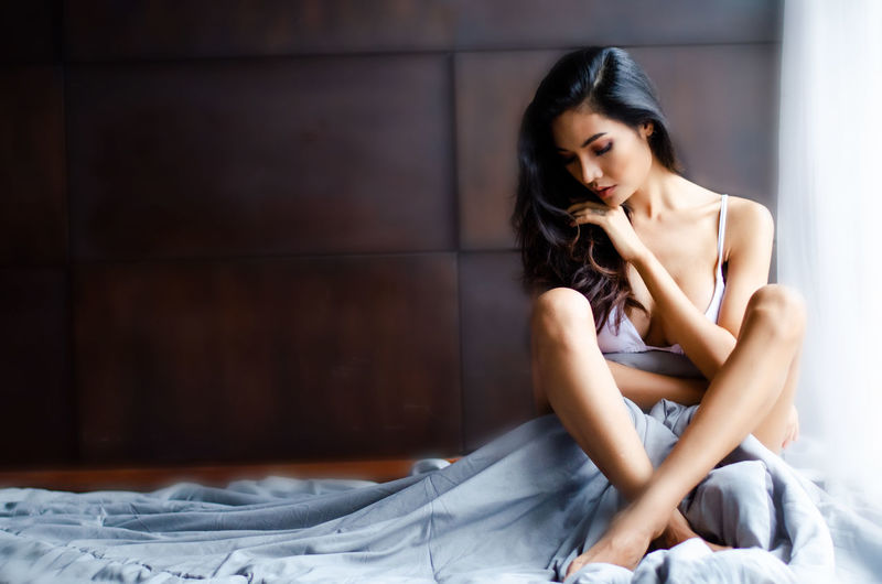 Sensuous young woman sitting on bed