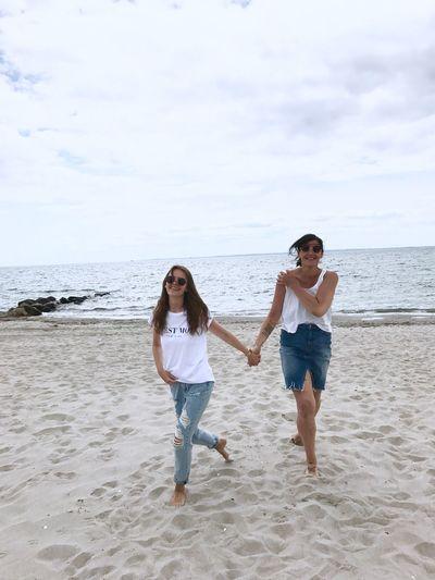 Portrait of smiling fiends walking at sandy beach