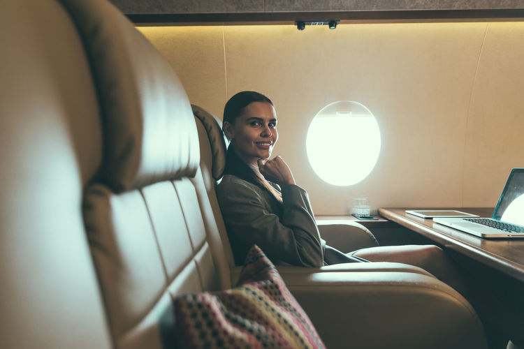 Portrait of smiling businesswoman using laptop in airplane