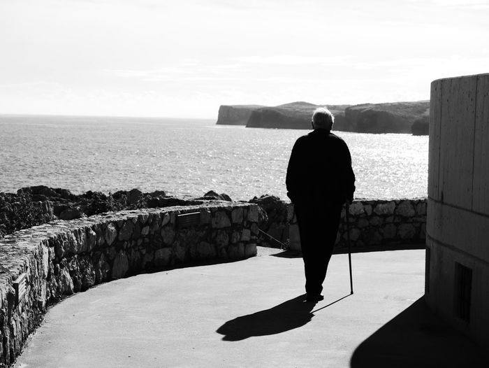 Rear View Of Silhouette Man Walking On Road By Sea During Sunny Day