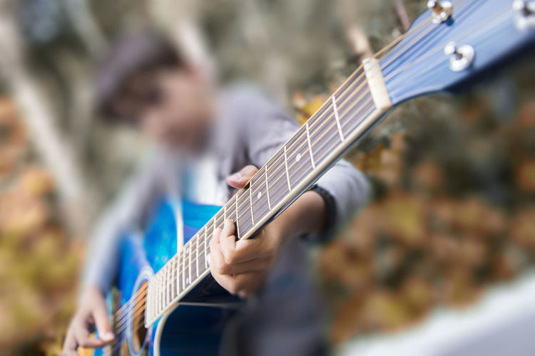 Playing guitar Day Guitar Human Hand Leisure Activity Music Musical Instrument Musical Instrument String Musician One Person Outdoors People Performance Playing Plucking An Instrument Real People Selective Focus