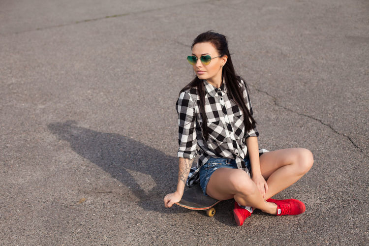 The woman with a totto on her hand and in glasses is sitting on the skate on the background of asphalt. Fashion Sunglasses Glasses One Person Beauty Full Length Beautiful Woman Hairstyle Young Adult Women Hair Adult Sitting Young Women Casual Clothing Clothing Portrait Long Hair Outdoors