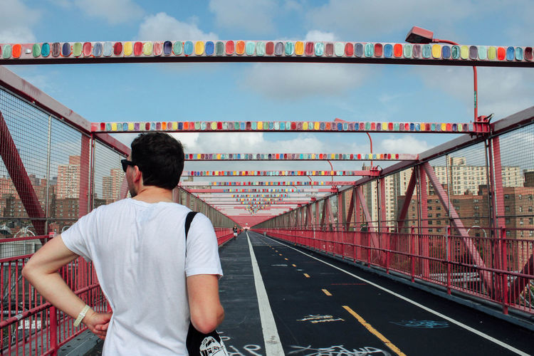 Rear View Of Man Standing On Williamsburg Bridge