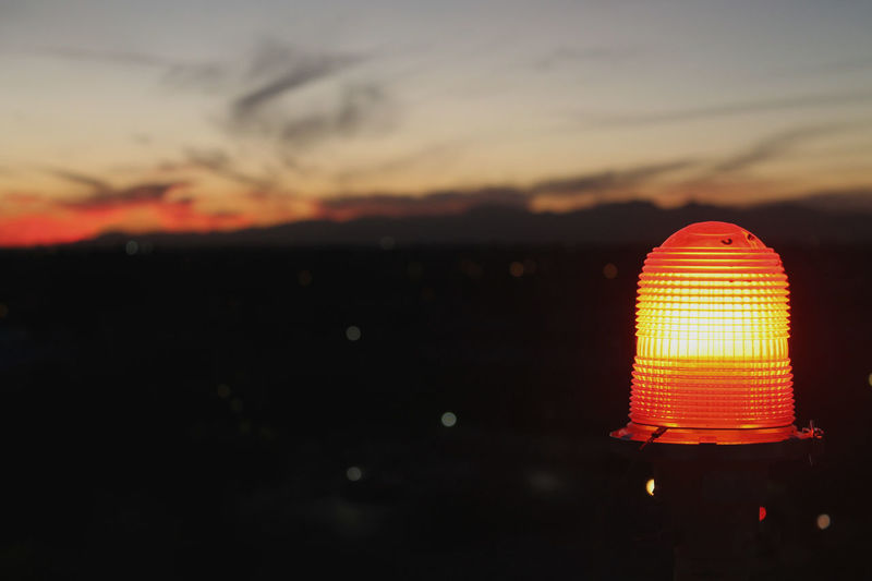 Close-up of illuminated lamp against sky during sunset