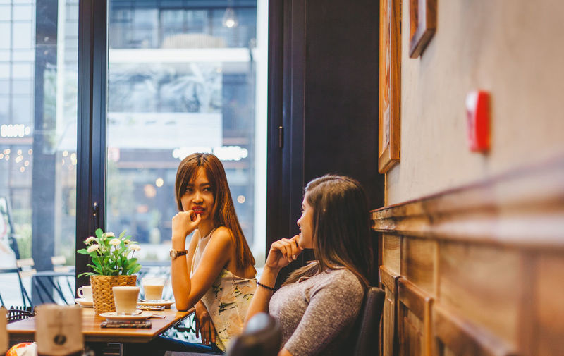 Adult Business Cafe Casual Clothing Coffee Shop Scene Drink Emotion Food And Drink Friendship Hairstyle Indoors  Leisure Activity Lifestyles Real People Restaurant Sitting Table Two People Window Women Young Adult Young Women