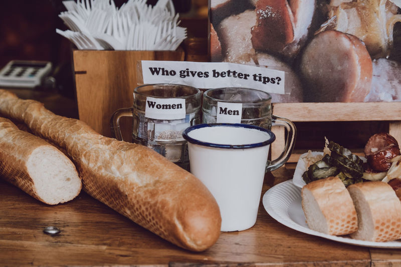 Close up of two tip jars standing on a counter near food, for men and women, asking who tips more. Glasses Cafe Question Sign Communication No People Close-up Indoors  Still Life Food Food And Drink Service Service Industry Tips Women Men Humour Bread Table Container Loaf Of Bread