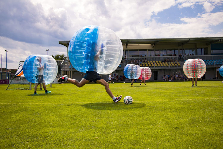 Men Playing Soccer With Zorb Balls On Field