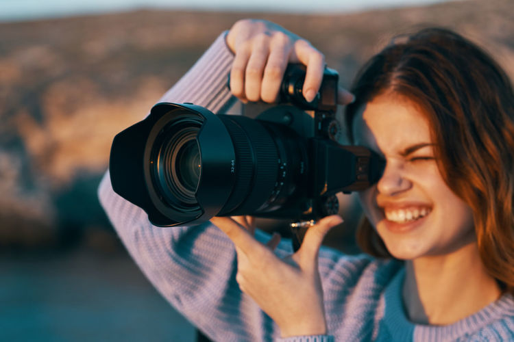 Portrait of smiling woman holding camera
