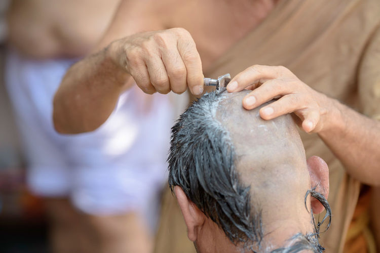 Midsection of barber shaving head of man