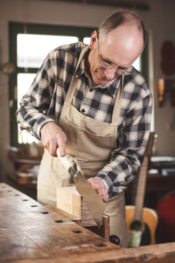 Mature craftsman using a Japanese double edged saw Artisan Hand Saw Sawing Japanese Saw Saw Work Tool Working Carpenter Professional Occupation Workbench Apron 50 Years Old Man Mature Adult Adult Concentration Skill  One Person Men Craftsperson Workshop Craft Indoors