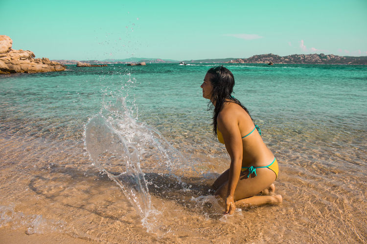 Side view of young woman in bikini kneeling at beach