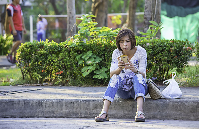 Woman using phone while sitting on seat against plants