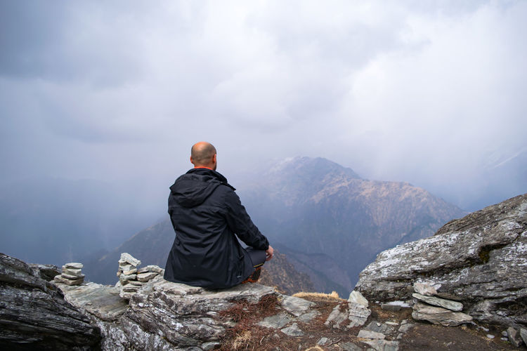 Rear view of mid adult man sitting on mountain against cloudy sky
