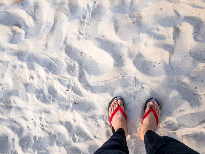 Men feet on the beautiful beach top view.Copy-space for editor. Adult Body Part Day Directly Above High Angle View Human Body Part Human Foot Human Leg Human Limb Land Leisure Activity Lifestyles Low Section Nature One Person Outdoors Personal Perspective Real People Sand Shoe Snow Standing