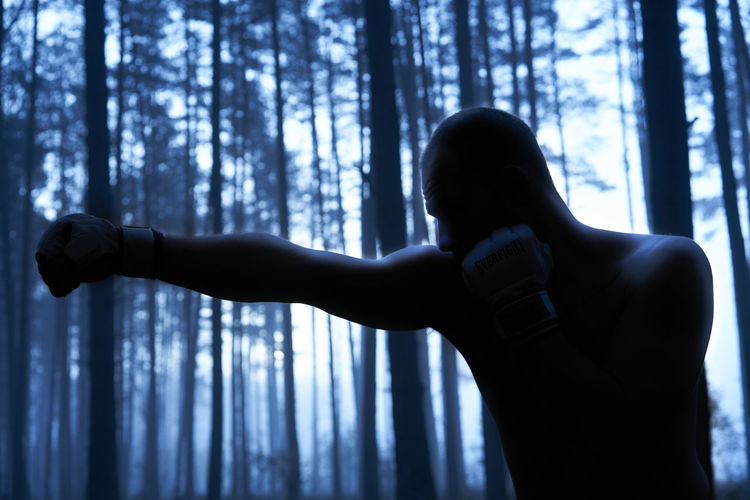 Shirtless silhouette man punching tree trunk in forest