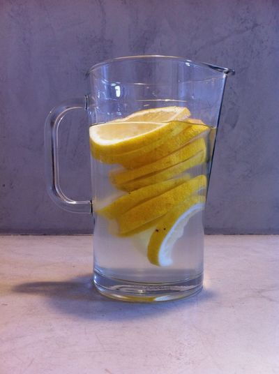 Low angle view of lemon slices and water in glass on table