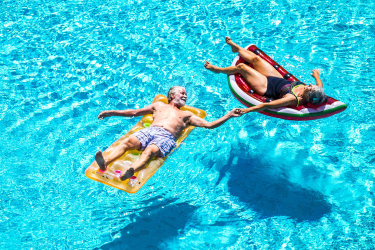 Happy relaxed people caucasian senior adult couple taking hands lay down with trendy coloured lilos on a blue water swimming pool during a summer holiday vacation - enjoying active retired lifestyle Above Active Activity Adult Aged Air Background Blue Caucasian Cheerful Colors Coloured Couple Elderly Enjoy Enjoying Floating Friends Fun Happiness Holiday Home Hotel Inflatable  Leisure Lilo Mattress Mature Old Outdoor People Playful Pool Recreation  Residence Resort Retired Senior Summer Sun Sunbath Swimming Swimming Pool Trendy Tropical Vacation Village Water Watermelon White