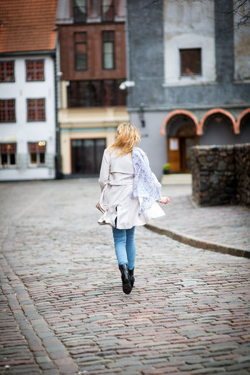 Old Town Adult Architecture Blond Hair Building Exterior Built Structure Casual Clothing City Cobblestone Day Footpath Full Length Hair Hairstyle Lifestyles Old City One Person Outdoors Paving Stone Real People Rear View Street Walking Warm Clothing Women