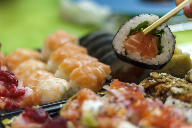 Eat sushi with Chopsticks Food Ready-to-eat Indoors  Sushi Roll Raw Raw Food Fish Seafood Japanese Food Cuisine Asian  Delicious Tasty Asian Food Freshness Selective Focus Chopsticks Rice Temptation Healthy Eating Maki Sushi Maki Sushi Time