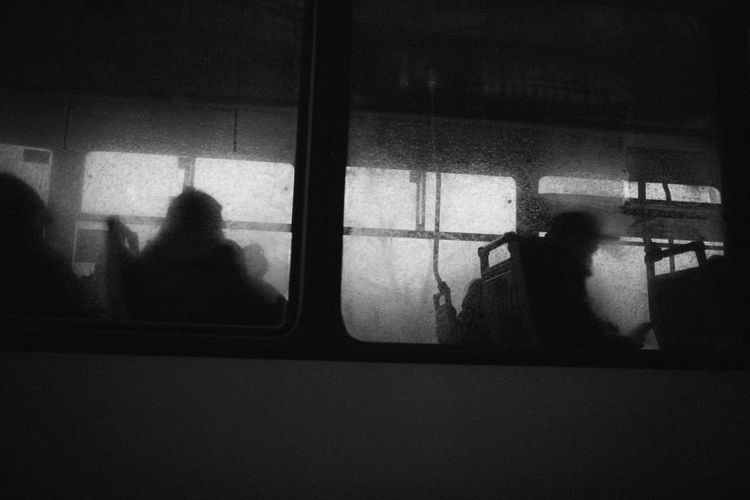 Silhouette people seen through train window