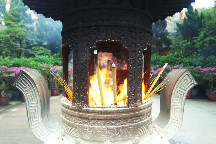 Architecture Burning Close-up Day Fire Flame Incense No People Outdoors Place Of Worship Religion Spirituality Temple Tree Worship
