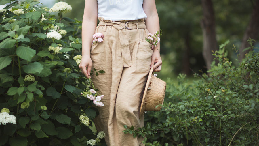 Midsection of woman standing by flowering plants