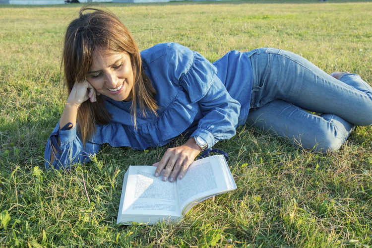Side view of a smiling woman lying on grass ground at park while reading a book Grass One Person Reading Lying Down Plant Publication Casual Clothing Field Relaxation Book Leisure Activity Land Young Adult Smiling Nature Young Women Women Three Quarter Length Hairstyle Outdoors
