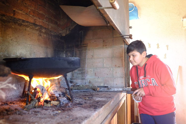 cocinando en disco de arado Burning Fire Fire - Natural Phenomenon Real People Young Adult Flame Lifestyles Wood - Material One Person Leisure Activity Indoors  Heat - Temperature Standing Front View Wood Day Young Women Young Men Three Quarter Length Preparation