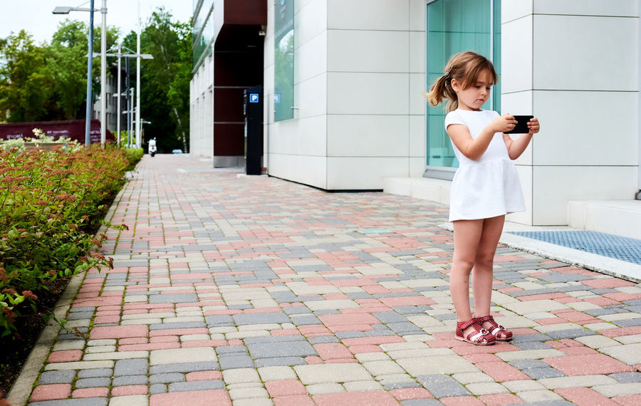 Little girl with a smartphone outdoors 5 Years Old Alone Beautiful Caucasian Cell Cellphone Child Communication Daughter Device Game Internet Kid Little Girl Looking Mobile Phone Network Outdoors Phone Playing Small Girl Smartphone Summer Technology Wireless Technology