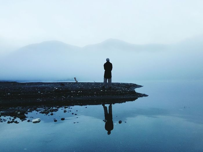 Man standing by lake overlooking misty mountains