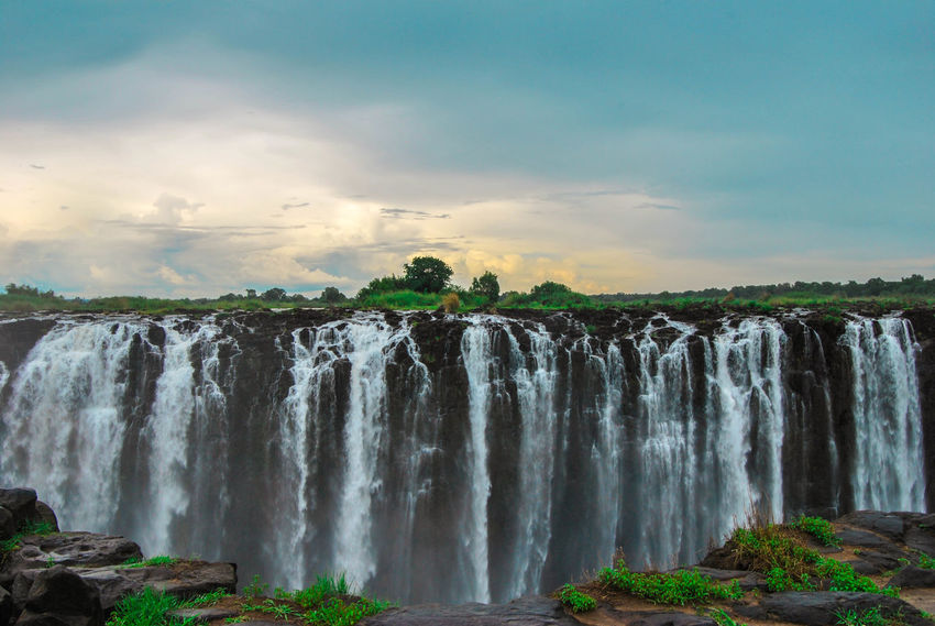 Beauty In Nature Blurred Motion Cloud - Sky Day Flowing Water Long Exposure Low Angle View Motion Nature No People Outdoors Power In Nature Scenics Sky Splashing Travel Destinations Tree Water Waterfall