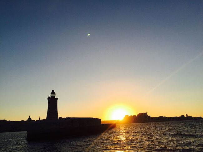 Sun Water Sunset Architecture Building Exterior Waterfront Built Structure Guidance Lighthouse Sea Protection Silhouette Orange Color Tower Clear Sky Lens Flare Scenics Outdoors Tranquil Scene Moody Sky