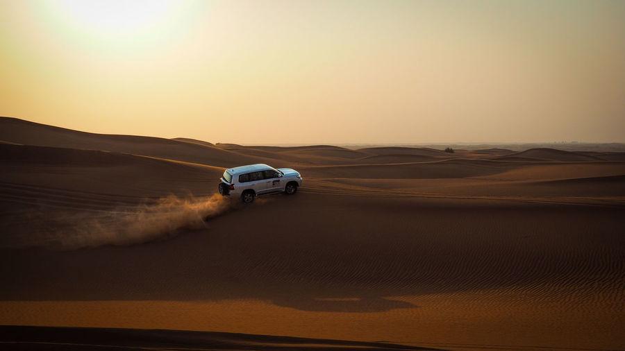 Car Moving On Desert Against Sky