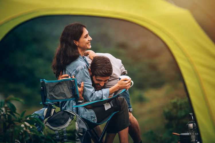 Smiling couple sitting by tent outdoors