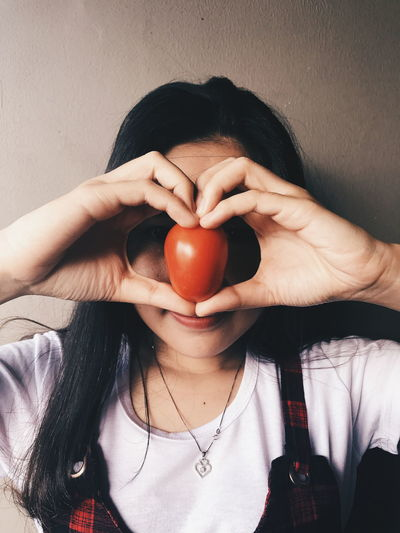 Close-Up Of Woman Holding Tomato Against Wall
