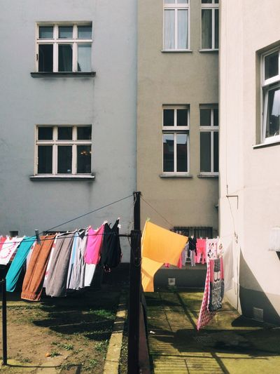 Fabrics drying on clotheslines outside building