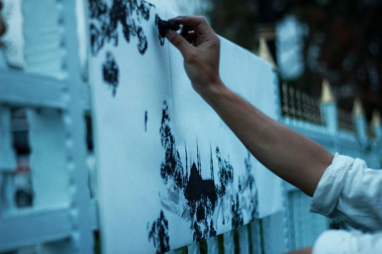 Cropped image of artist painting on fence