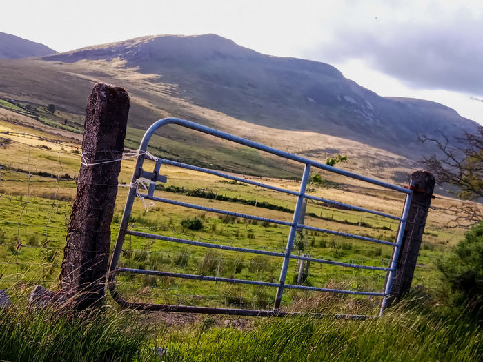 Fence on field by mountains against sky