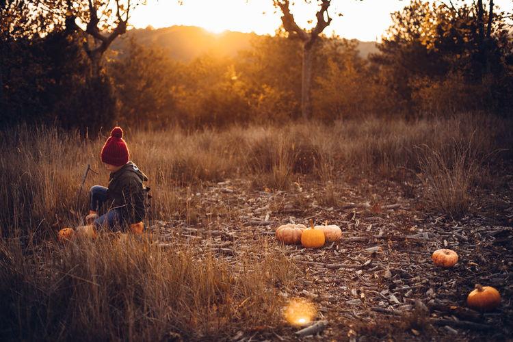 Full length of man sitting on field against sky during sunset