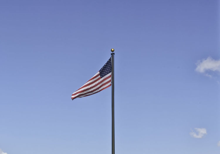 An American flag on a black metal pole weaving in the clear sky on the 4th of July. Stars and stripes on a background ideal for copyspace. Concept for independence, freedom and patriotism American Democracy Freedom Isolated Memorial National Patriotic USA Unity America Banner Fabric Flag Flagpole Flap Glory Indipendence Labor Nation Patriotism Pole Pride Stars And Stripes Striped Symbolic