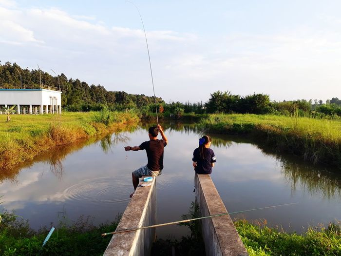 Rear view of man fishing with daughter in lake against sky