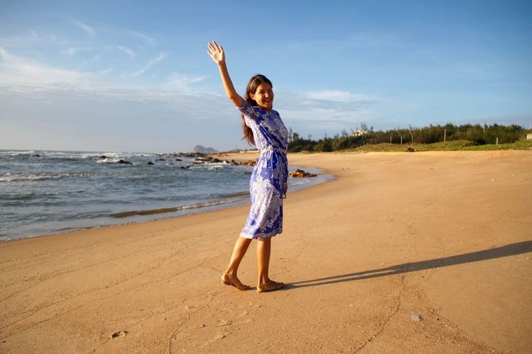 Side view portrait happy woman waving while standing at beach